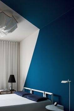 Un gioco di geometrie di colore blu turchese che coinvolge parete e soffitto è una perfetta decorazione per questa stanza da letto