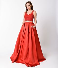Slip into this fabulous red two piece gown for your upcoming senior prom and be the life of the party! This red dress is a crop top style with beads galore! The front side of the top also has a design that resembles a peacock tail in a solid red color fil