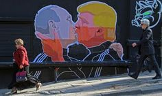 People walk past a mural on a restaurant wall depicting Donald Trump and Vladimir Putin greeting each other with a kiss in the Lithuanian capital Vilnius.