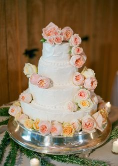 Spackled wedding cake adorned with a cascade of garden roses