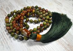 Unakite Buddhist Prayer Beads, made of 8mm unakite and aventurine beads. and gold metal markers, finished green tassel. Guru bead - red jasper. The 8mm beads are hand knotted one at a time on a strong green silk thread. Lenth with tassel - 26 inch About Unakite Jasper: Jasper is