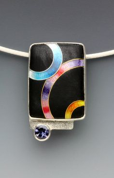 Anna Tai Small Rings Pendant  cloisonne pendant is hand fabricated with enamel, fine silver, sterling silver, 24k gold, and a 5 mm round faceted iolite. The black opaque enamel is etched to create a matte finish that contrasts strikingly with the high gloss of the colored enamel. A 1.8mm sterling silver cable wire with tension clasp is included. Artful Home