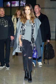 Copy Jessica Alba's stylish travel style with ripped jeans, a cozy tee, and drapey coat.