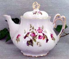 Lovely hummingbirds on a blackberry stem are the featured motif on this fine porcelain teapot.  Hand decorated in the U.S., this teapot holds 6 cups and has a dainty openwork handle.   Accessories are also available.