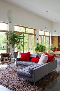 Uma parede de janelas de vidro isolante banha a área de estar em luz, e o teto alto faz a área de 150 metros quadrados parecer maior.  Fotografia: Trevor Tondro / The New York Times.