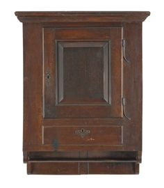 """Sold $10,000  Pennsylvania walnut hanging cupboard, ca. 1750, probably Lancaster County, the molded cornice over a raised panel door with original rattail hinges, above a single drawer and an open shelf with spurred sides, 38 1/4'' h., 26'' w.  Condition Depth - 10 1/2"""". Brass replaced, escutcheon replaced. Nice old dry surface. Very good condition. No other apparent condition issues."""