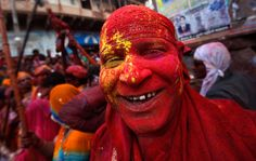 """A man daubed in colored powder poses for a picture during """"Lathmar Holi"""" at Barsana in the northern Indian state of Uttar Pradesh"""