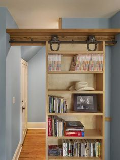 Sliding Bookcase Wall to die for. How cool would this be to close odd the end of the house where the bedrooms are?: