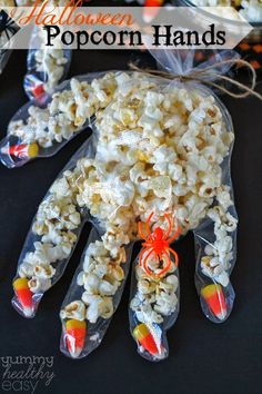 Fun Halloween craft to make with kids! Disposable gloves with candy corn fingernails, filled with popcorn. So cute!