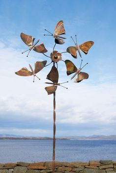 This kinetic art sculpture features butterfly wings is 5 1/2' tall and is made of copper. The wind spinner is available in flamed copper, blue,...