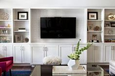 Transitional living room features a wall to wall white built in shelving unit lined with a flat screen TV and grey trellis wallpaper on the back of shelves.