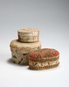 THREE SMALL WALLPAPER BOXES, TWO WITH PINCUSHION TOPS AND ONE WITH ORIGINAL LABEL.