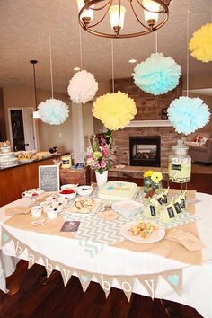 We love the decor! Chalkboard details and baby blue poms to match the baby shower invitation from Tiny Prints.