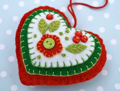 Handmade felt heart ornament with layers of applique and embroidery in green, red and white, embellished with tiny buttons.  A special handmade felt Christmas ornament.  9cm x 8cm/3.5 x 3 inches approx, with a cotton loop for hanging.