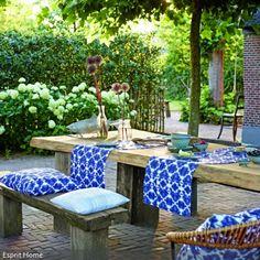 Mit blau gemusterten Kissen und Tischläufern wird aus dem robusten Essbereich eine sommerliche Sitzecke. Dazu passend: Blumendeko in Glasvasen.
