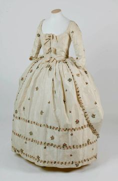 Robe à la Polonaise, 1760. Cream sprigged and brocaded silk with original moiré bows and fly braid trimming.