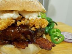 Beast Mode burger gets its namesake from Seattle Seahawks running back - Marshawn Lynch. This Super Bowl tribute burger is 10 oz and is topped with fried panko crusted Havarti cheese, candied cayenne bacon, roasted garlic mayo, and other goodies. Visit my website, The Burger Nerd, for the full recipe. #hamburger #cheeseburger #superbowlrecipes