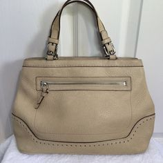 """🎉HP🎉 Leather Coach Bag Polished, professional and pretty all describe this leather Coach bag. Plenty of pockets including outside and inside zip with a separate phone pocket. Zip top with cute tassel trim. And the bottom has feet!! Approx measurements: 12"""" across x 8.5"""" high x 5"""" deep. Overall the bag is in excellent condition but due to the light color it has a few minor cosmetic blemishes. Note: I'm poshing this for my Mom. Her home is 🔥🐱free but has a 🐶. Sorry no trades or PayPal…"""