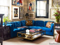 In the family room of a Manhattan apartment designed by Miles Redd, a sectional purchased at Christie's is covered in a blue cotton velvet by Schumacher. The Nobilis Chene faux-bois paper on the walls is hung horizontally for a modern look. Pillow fabrics, Old World Weavers. Vintage coffee table, Mecox.