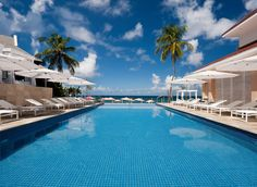 BodyHoliday Saint Lucia Cap Estate, Caribbean All-Inclusive Resorts Beach Hotels Luxury Travel Solo Travel sky building water Resort swimming pool property Pool leisure resort town palm tree home Villa arecales condominium Sea leisure centre blue caribbean amenity swimming