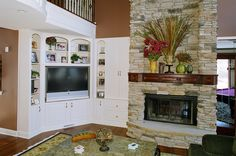Custom built-ins make thorough and efficient use of every nook and cranny in a house, even those awkward corners! This corner entertainment unit makes for a beautiful way to display a television and personal decorations, as well as storage for anything you want to tuck away out of sight, and perfectly uses every bit of space between this hallway and stone fireplace.  #white #stone #mantle #fireplace #den #living #room #storage #corner #entertainment #center #tv #television #console #stereo