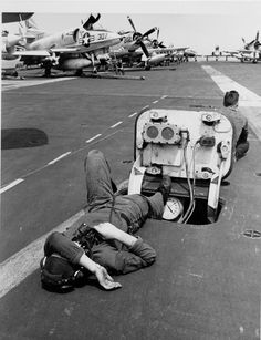 A member of the flight deck crew on board the carrier Coral Sea (CVA 43) takes a short rest during a lull in flight operations on board the carrier operating on Yankee Station off the coast of North Vietnam