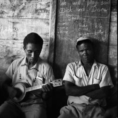Jamaican Men with Banjo A Jamaican man plays the banjo for his friend as they sit below a blackboard filled with children's spelling lessons.    © Bradley Smith/CORBIS