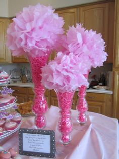 pom poms in vases with pink crinkle filler - ok maybe black and fuchsia. pretty for bridal shower.