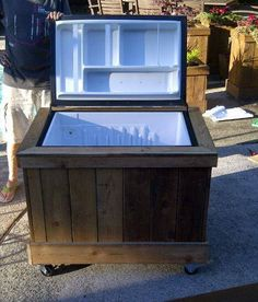 """They used a broken bar fridge, removed all of the electrical """"stuff"""" and added a tub drain to the back of the fridge I which is now the bottom of the cooler. Trimmed it out in a cedar box and put it on castors. It is so much better than most coolers - the ice stays frozen for well... a week so far and the former wire shelves have become dividers for pop, wine, etc."""