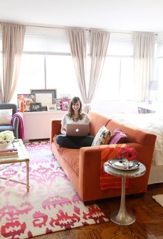 @Nikki Rappaport Home Tour // orange couch // studio apartment layout // beige walls // colorful accents // photo by Sarah Winchester Studios