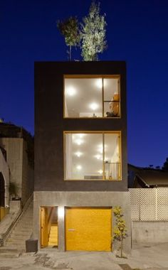 Large Stacked Windows and yellow framing open up the small Eel's Nest Residence in Los Angeles by Anonymous Architects