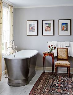 At a Long Island home reimagined by architect Kevin Lindores and designer Daniel Sachs, the tub in the master bath is by Waterworks, the Indian watercolors were purchased at Rago, the curtains are of a Chelsea Editions linen-cotton, and the walls are painted in Farrow & Ball's Elephant's Breath | archdigest.com