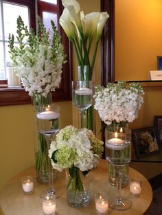 Glass cyldiners designed in white... calla lillies, snap dragons, andstock with a cyldiner of white and mini greenhydrangea surrounded by pedestals with floating candles and votive candles.   Doristhefloristt.com