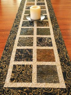 This dramatic batik table runner is a statement piece for your home in black and golden brown batik prints from the Madrid collection by Timeless
