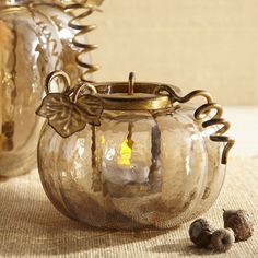 For anyone who loves fall, candles and pumpkins, our tealight holder is a real treat. In the spirit of traditional jack-o'-lanterns, our handcrafted glass pumpkin features a lustrous amber finish and a hollow core. The golden, powder-coated iron holster is removable, making it easy to insert your favorite tealight. And that's no trick.