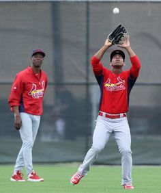 Cardinals outfielder Oscar Taveras catches a fly ball in a fielding drill during St. Louis Cardinals spring training on Friday, Feb. 15, 2013, at Roger Dean Stadium in Jupiter, Fla. At left is instructor Willie McGee.