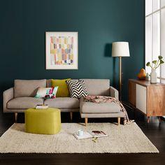 Mur bleu canard (foncé), canapé gris, pouf et coussin jaune/vert anis et graphique (chevrons noir