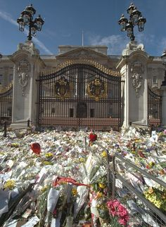 The main gate to Buckingham Palace was also covered in flowers, meaning the changing of th...