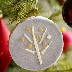un petit ornement en feutre blanc décoré comme un arbre pour Noël