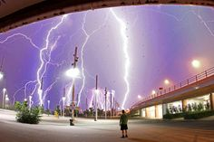 Lightning storm through the purple sky (and who is that guy?  Is he too stupid to go inside!).