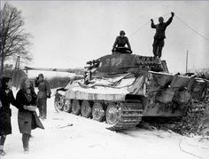 Two American soldiers inspect a destroyed German King Tiger tank, Belgium, 1944. Also they're all admiring the three passing girls. Photo taken near the village of Corenne, Belgium, 1944.