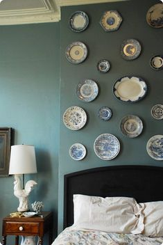 displaying vintage plates over a bed.