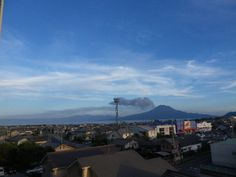 2013年7月14日  今日の桜島上空は西向きの風。白いのは普通の雲。黒ずんでいるのは噴火によって吹き上げられ風に流されている途中の火山灰。大隅半島の鹿屋市あたりに降ると思われる。