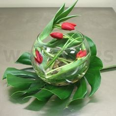 Modern and elegant centerpiece with tulips in a glass bowl with river stones. Here you see Monstera leaves used as placemats for the centerpiece