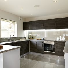 The open-plan kitchen and dining room is divided by a breakfast bar. French doors lead onto the garden. #Strata