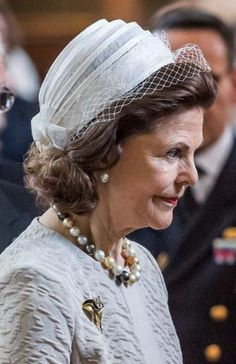 Queen Silvia, repeated her pleated white straw calot hat with back bow and white net veil for the occasion.