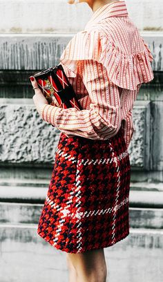 A striped Miu Miu ruffle blouse is paired with a houndstooth skirt and Louis Vuitton clutch