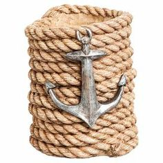 """Stow your favorite vintage in nautical-chic style with this charming bottle holder, crafted from rope and showcasing an anchor accent.   Product: Bottle holderConstruction Material: Rope and metalColor: Natural and silverFeatures: Holds one bottle of wineAnchor accentCoiled rope designDimensions: 6.1"""" H x 4.91"""" Diameter"""