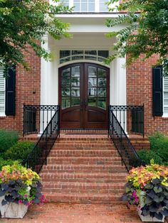 Mixed planters with pinks and deep purples set the foundation for this picture-perfect entryway. The containers are at the bottom of brick steps and a black wrought iron railing that lead to a brown double door with glass panels. Front Entrances, Sliding Glass Door Window, Traditional Front Doors, Front Door Colors, Entrance Doors, Double Door Entryway, Wrought Iron Front Door, Brick Steps, Red Brick House