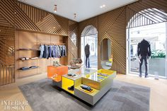 Custom oak latticework defines the menswear department, where a Patricia Urquiola chair upholstered in a Missoni wool sits in a corner. Photography by Patricia Parinejad. Interior Design Magazine, Retail Interior Design, Retail Store Design, Boutique Interior, Commercial Interior Design, Commercial Interiors, Retail Stores, Ikks Kids, Patricia Urquiola